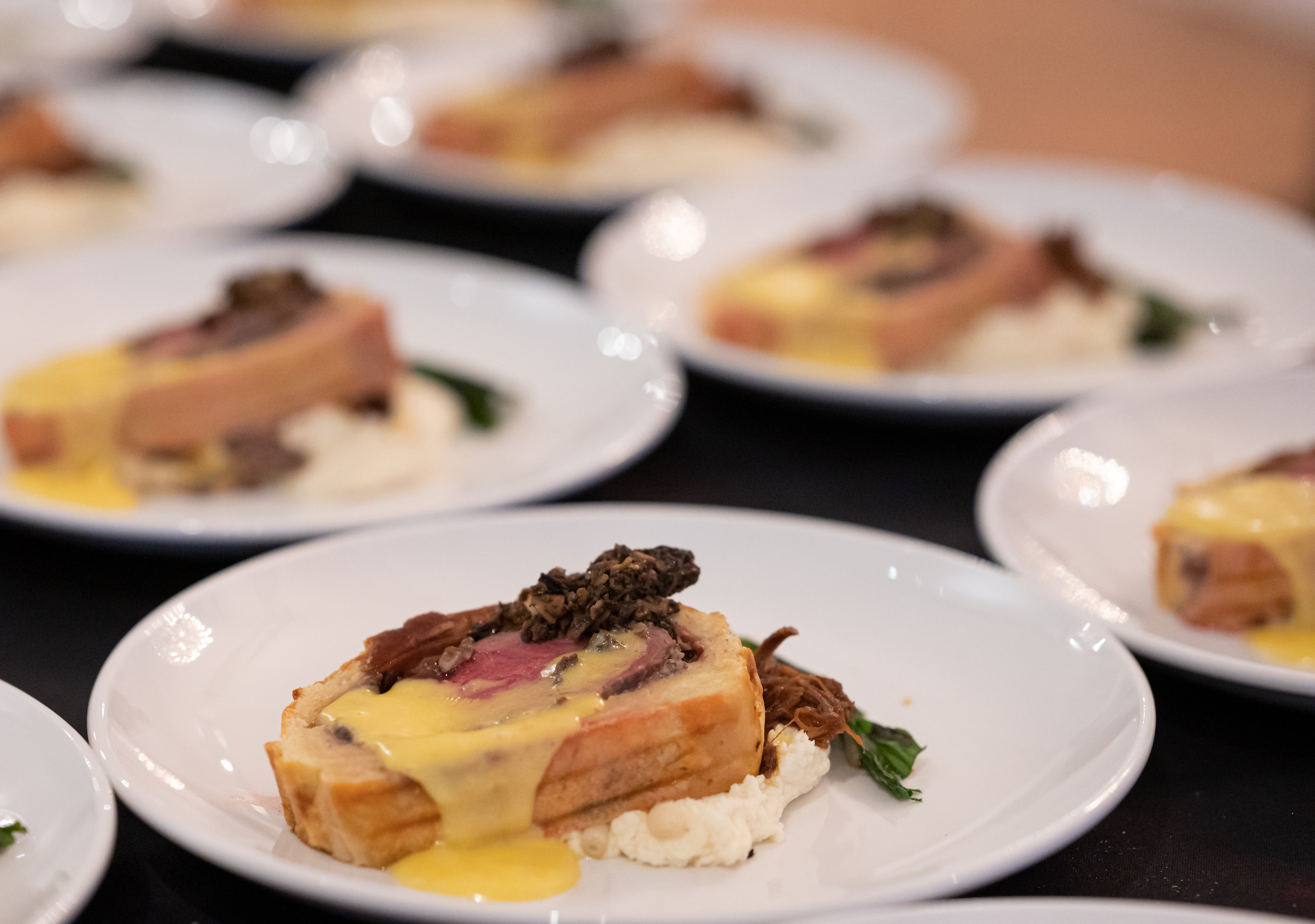 Certified Angus beef wellington over braised short ribs with sauteed morels, charred ramps, celery root-horseradish puree and hollandaise