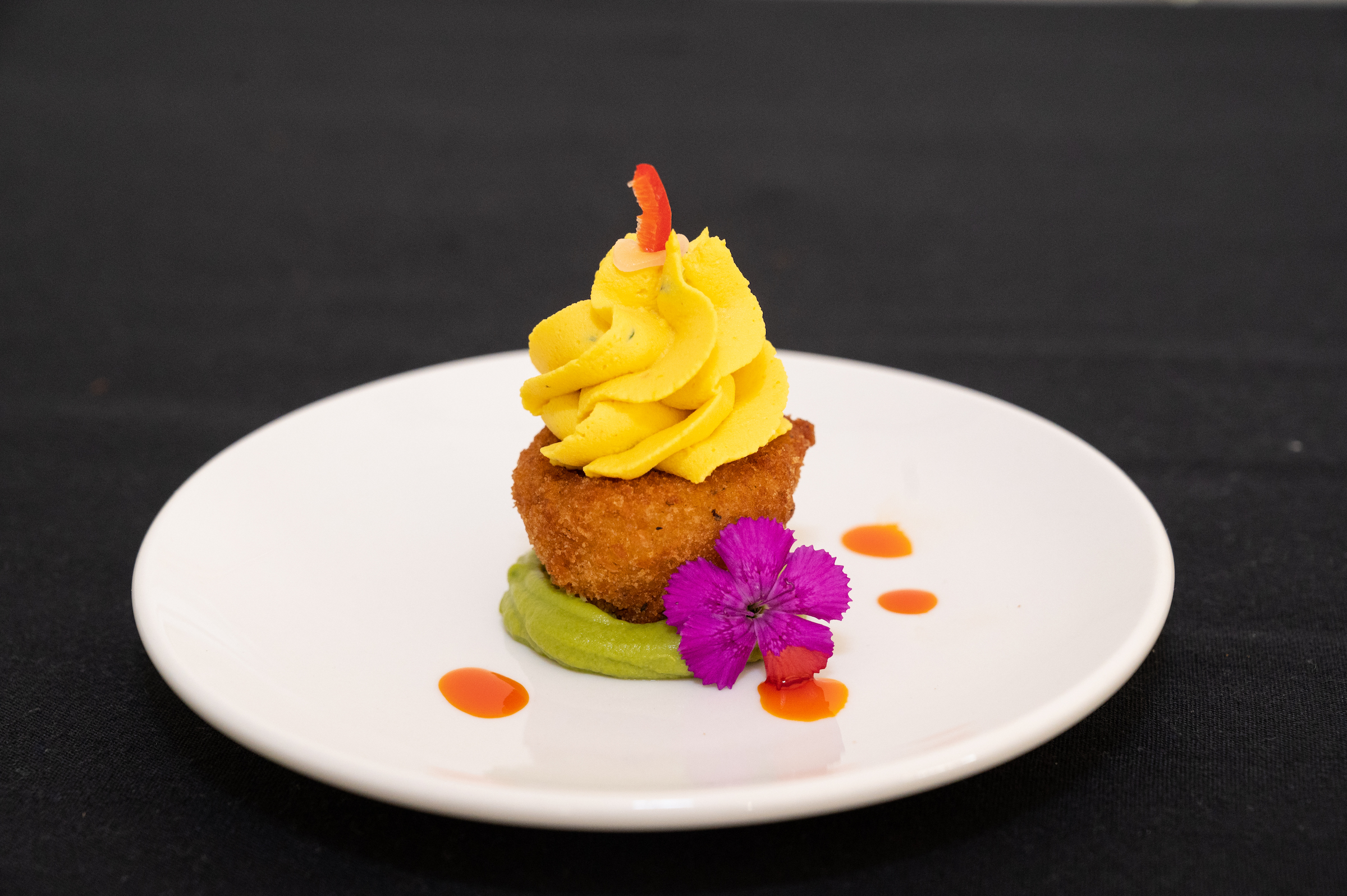 Fried deviled egg over avocado puree with pickled Fresno pepper